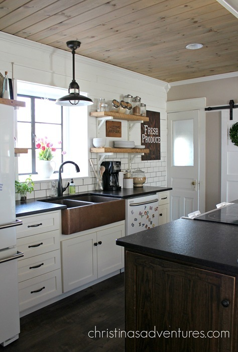 A beautiful hammered apron front farmhouse copper sink centers this farmhouse style kitchen. It pops against the white cabinets, subway tile and open shelving