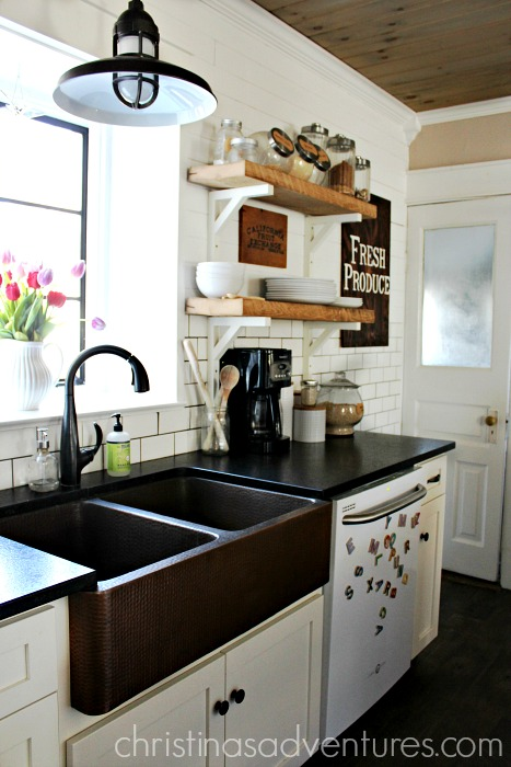 leathered granite counter tops with a copper sink in a farmhouse kitchen