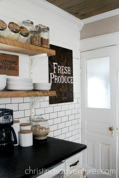 farmhouse kitchen with open shelving wood ceiling and black countertops