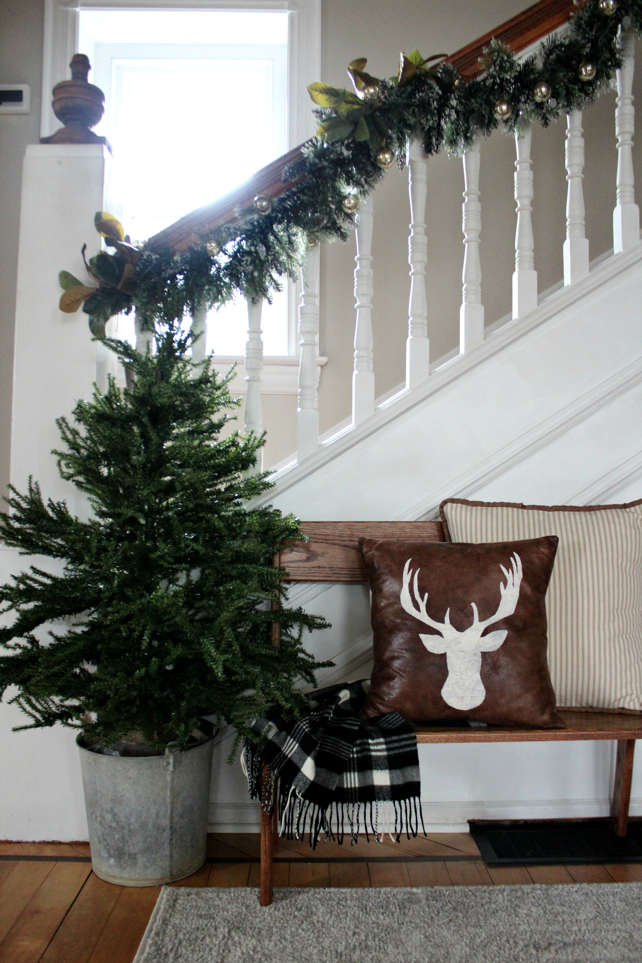 christmas tree in a bucket with stair garland Farmhouse Christmas Hallway Decorating Christinas