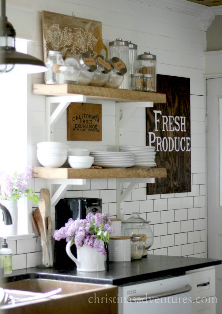 lilacs in the farmhouse kitchen with open shelving and subway tile halfway up the wall