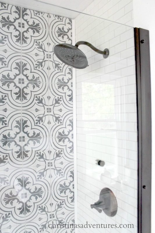 black and white patterned tile walk in shower with a gooseneck rain shower head and subway tile
