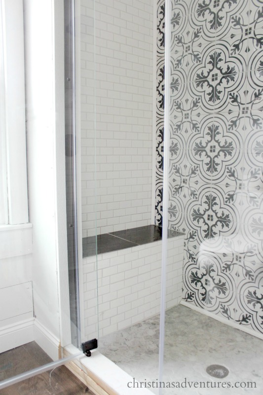 built in shower seat bench glass shower door patterned tile and subway tile
