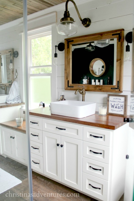 vintage inspired farmhouse bathroom with white cabinets and butcher block countertops, shiplap walls and gooseneck lighting