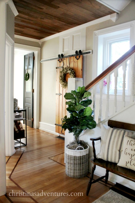farmhouse summer entryway with reclaimed wood ceiling, old wood barn door and original wood flooring