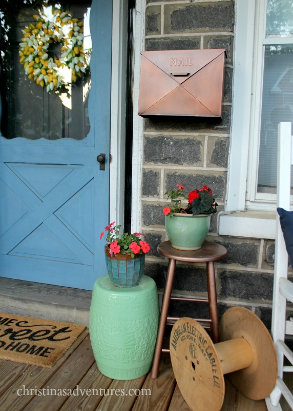 Copper mailbox on a front porch of a stone house with a blue door