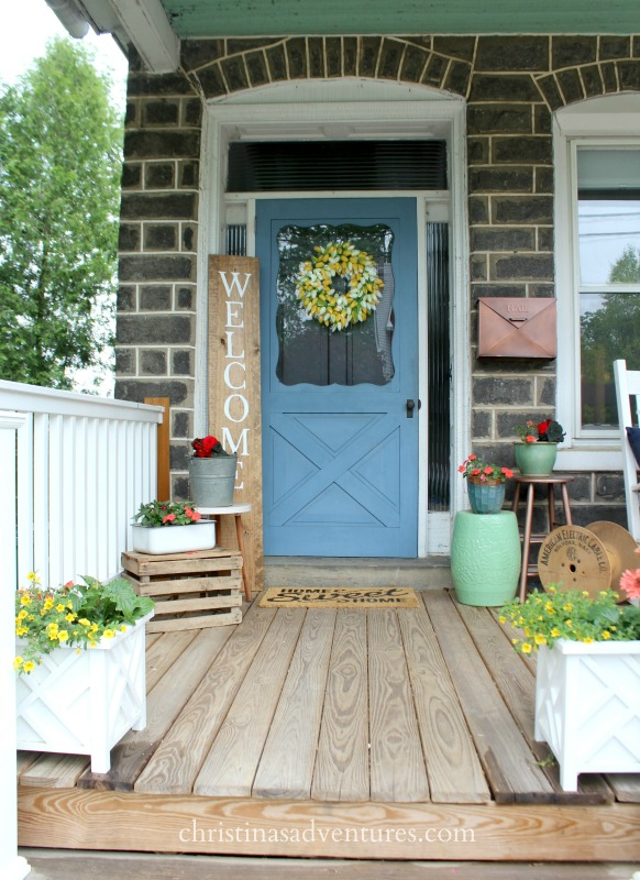 Summer front porch decorating on an old stone fixer upper house with a large welcome sign