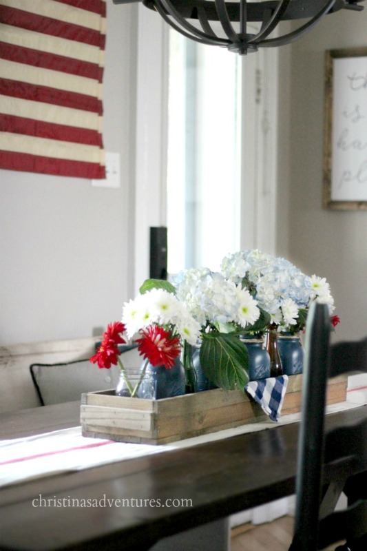 This simple 4th of July table combines a casual vintage feel with mason jars, an antique box, vintage flag and fresh flowers