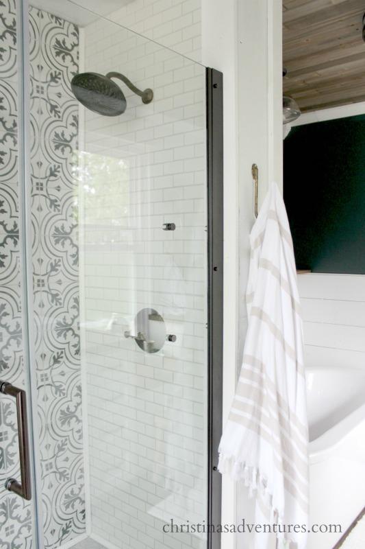 subway tile shower glass door patterned tile and gooseneck shower head wood ceiling