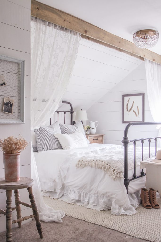 Love Grows Wild Farmhouse Bedroom With Wood Beam And Lace Curtains