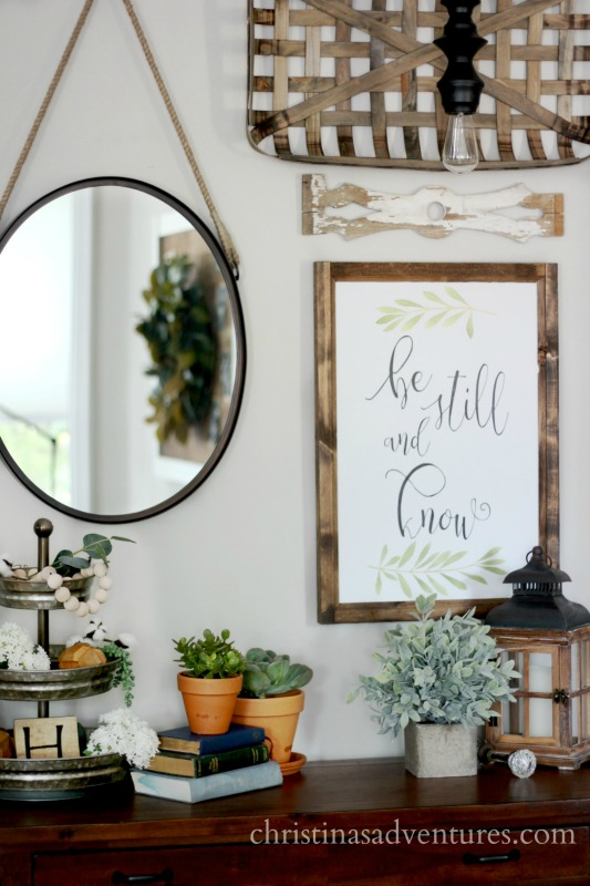 Farmhouse family room styling gallery wall with tobacco basket mirror tiered tray and greenery