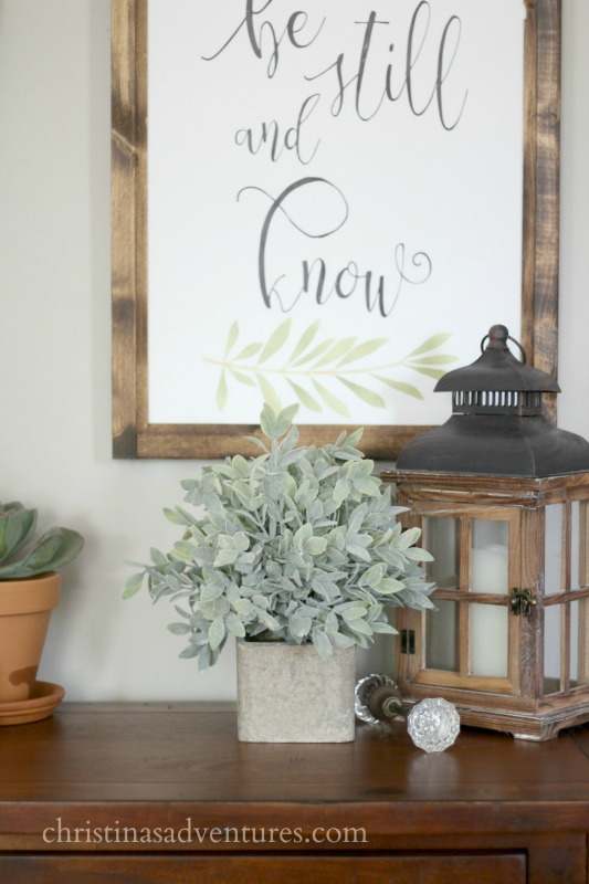 faux sage greenery wood sign and a wood lantern