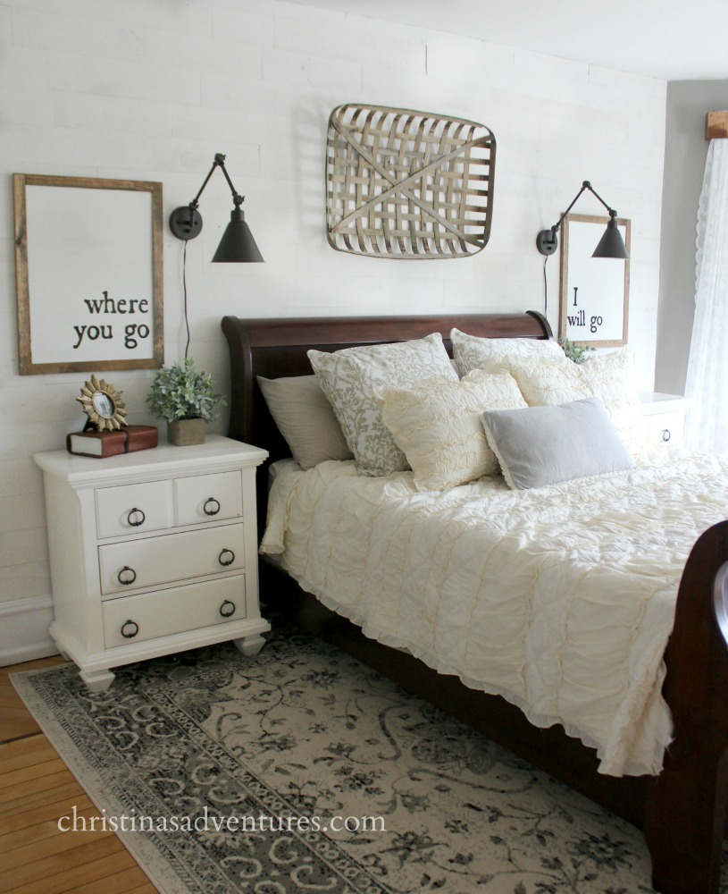 Farmhouse bedroom with white Stikwood wall behind the bed, black sconces and tobacco basket with ruffled bedding on a sleigh bed