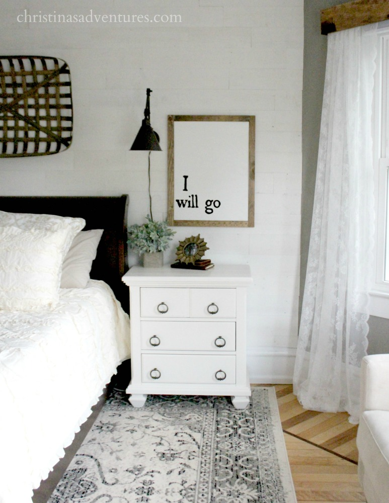 right side of bed with lace curtains
