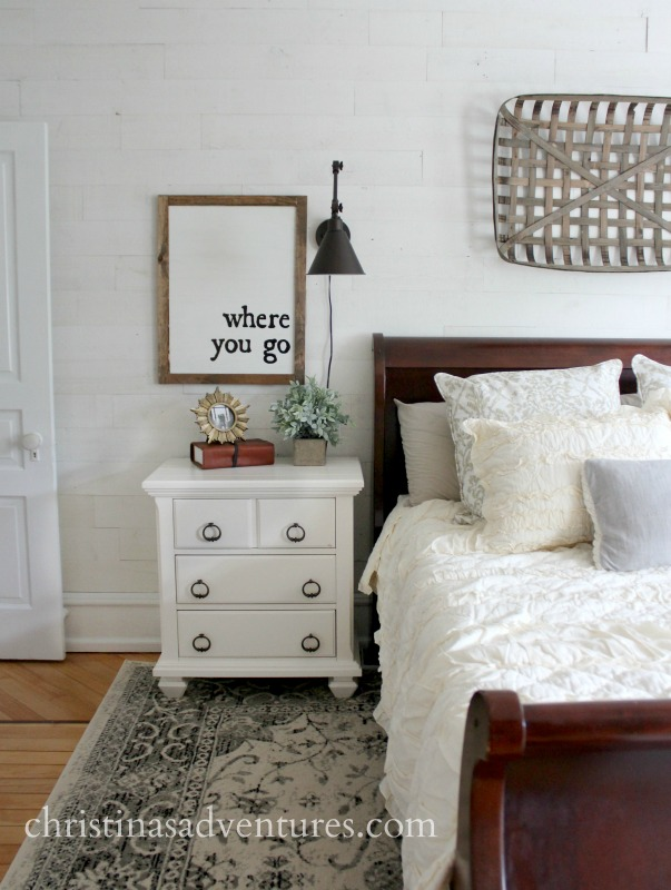 farmhouse inspired bedroom with shiplap walls and a tobacco basket over the bed