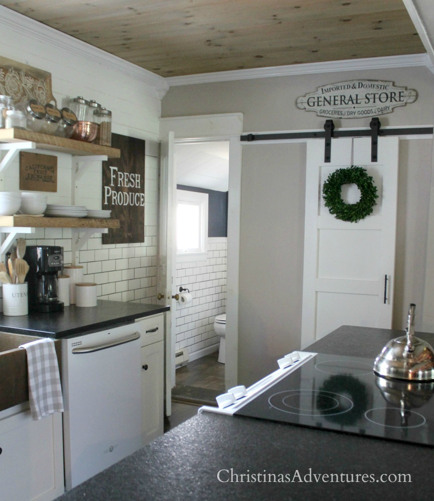 farmhouse kitchen barn door pantry with open shelving and wood planked ceiling