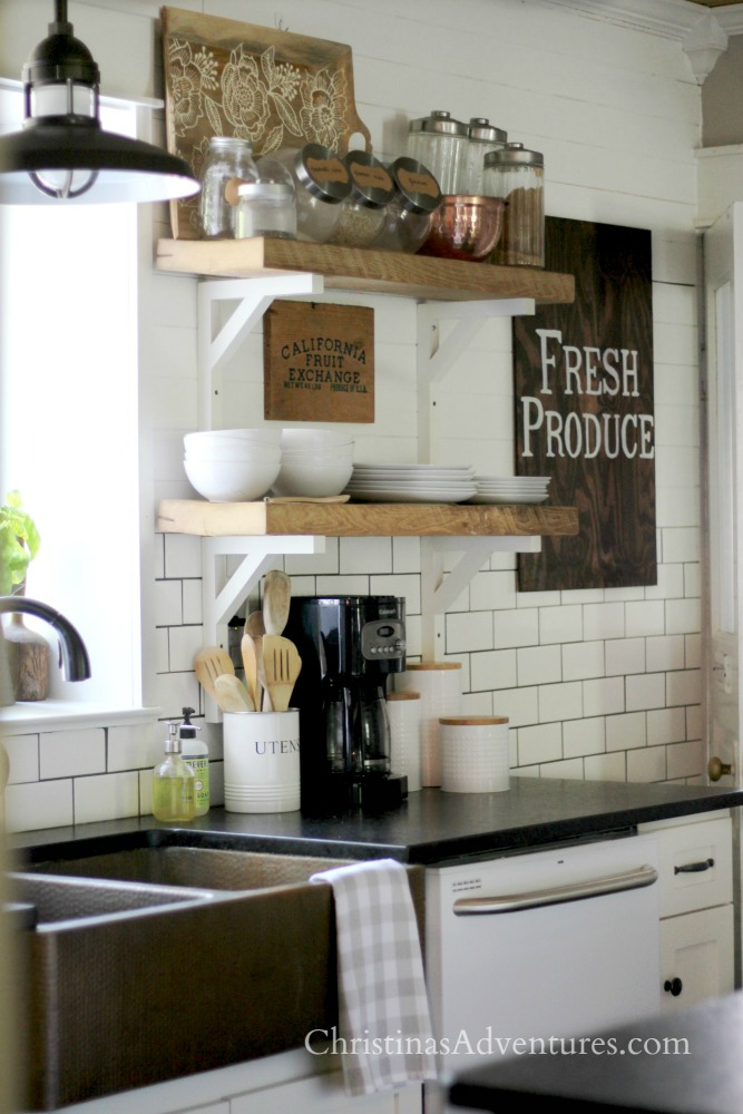 Farmhouse kitchen decorated for fall - chunky open shelving, subway tile and shiplap. Love the white cabinets, black countertops and copper sink