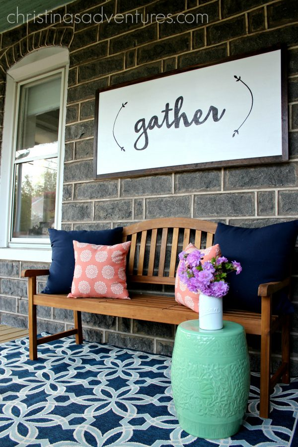 porch of a stone house with a large gather sign and blue indoor outdoor rug