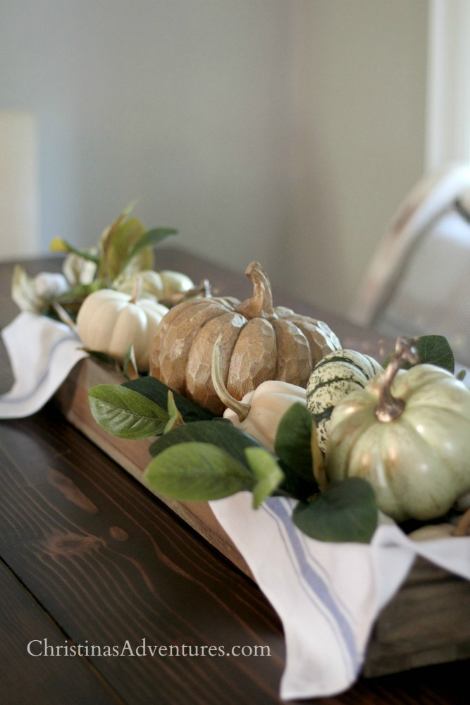 pumpkin fall centerpiece in a long wood box with magnolia leaves