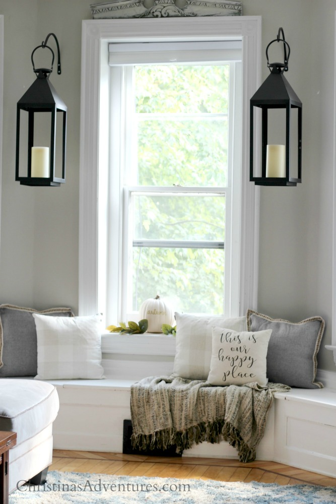 window seat throw pillows with lanterns between the windows