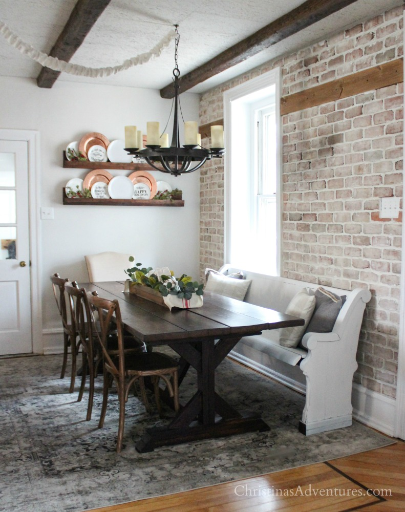 Brick wall dining area with wood beams a farmhouse table and a pew