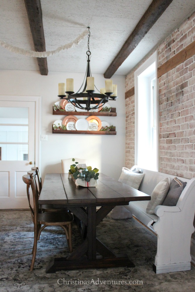 farmhouse chandelier over wood farmhouse table with brick wall and a white pew