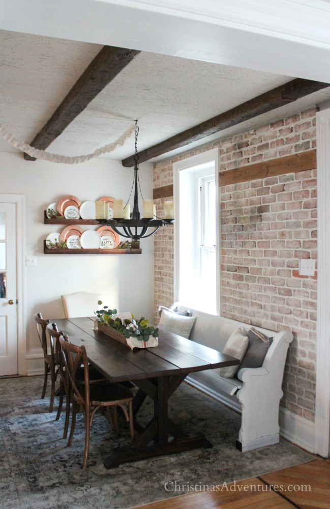 farmhouse dining room with brick wall plate shelf farmhouse table and white pew
