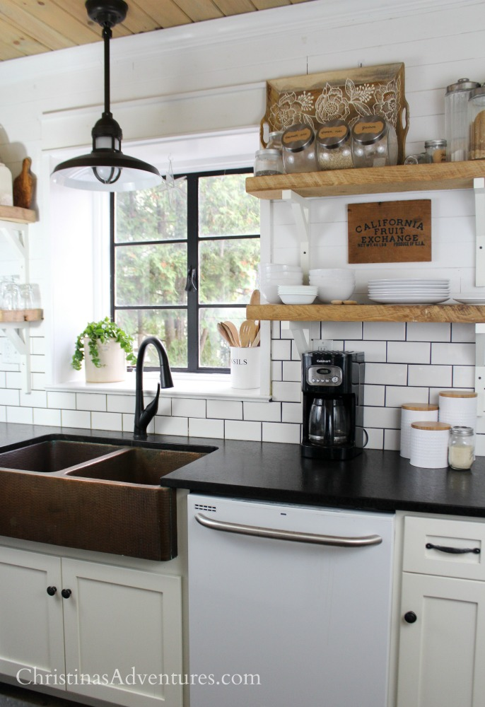 farmhouse kitchen with white subway tile backsplash and dark gray grout and shiplap on the top half of the wall