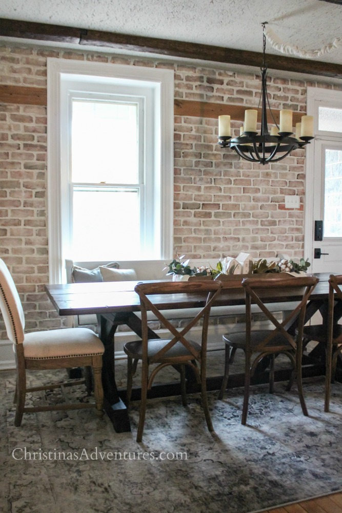 farmhouse table with brick veneer wall and x-back chairs