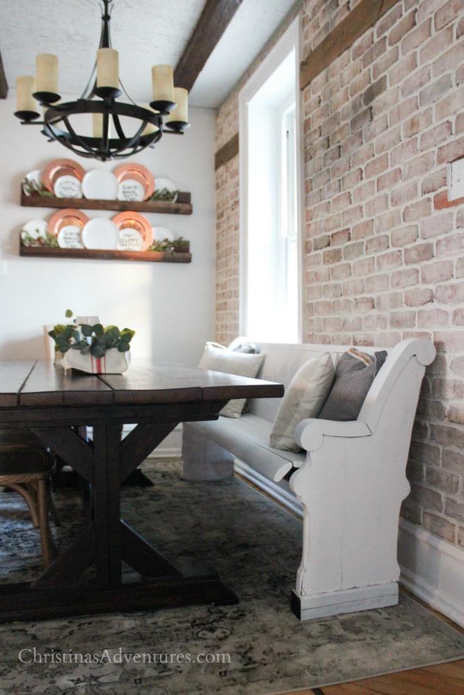 farmhouse table wood beams brick wall and pew