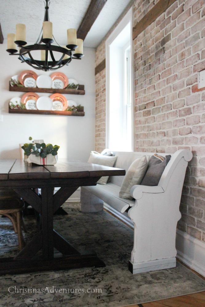 farmhouse table wood beams brick wall and pew