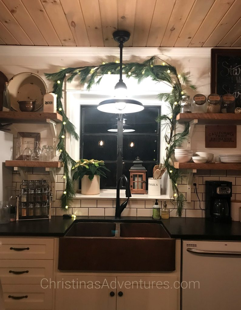 Farmhouse Christmas kitchen with fresh greenery over the window