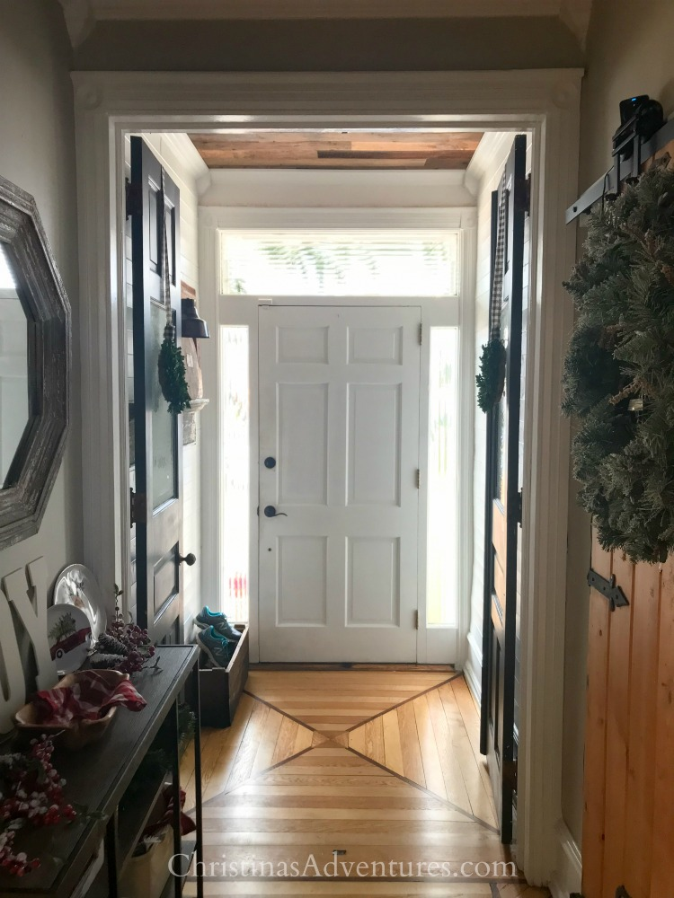 old house entryway with original wood floors and wood planked ceiling