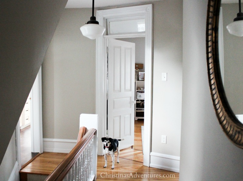 neutral hallway paint color with schoolhouse light and white trim