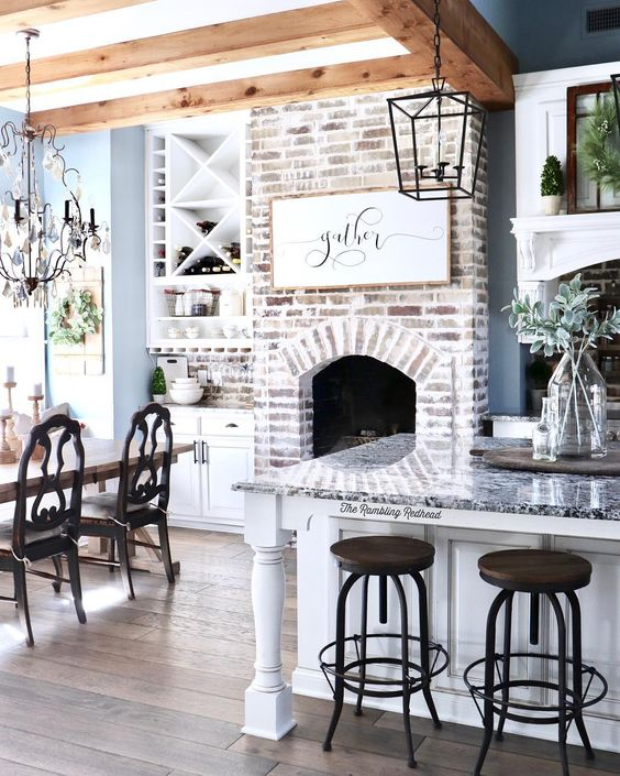 modern farmhouse kitchen with oversized island wood beams and functional brick fireplace