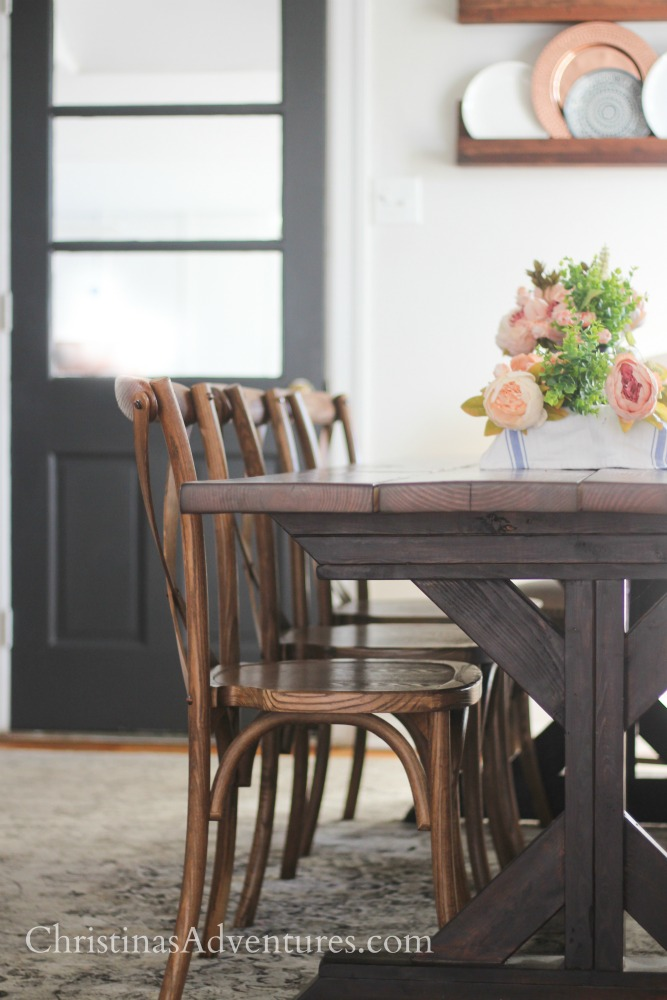 DIY farmhouse table with x-back dining chairs and spring flowers