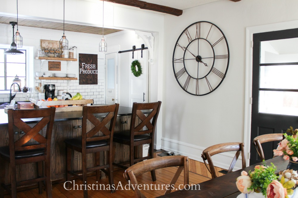 Farmhouse kitchen open concept interior design idea with black door and barn door pantry with oversized island and clock