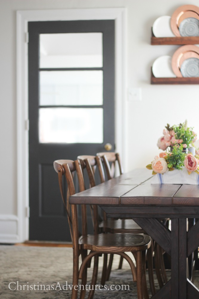 farmhouse table with neutral walls and dark gray painted interior door