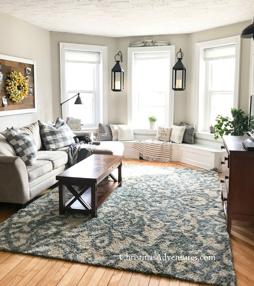 family room design with window seat and lanterns between the windows with blue and white shag area rug