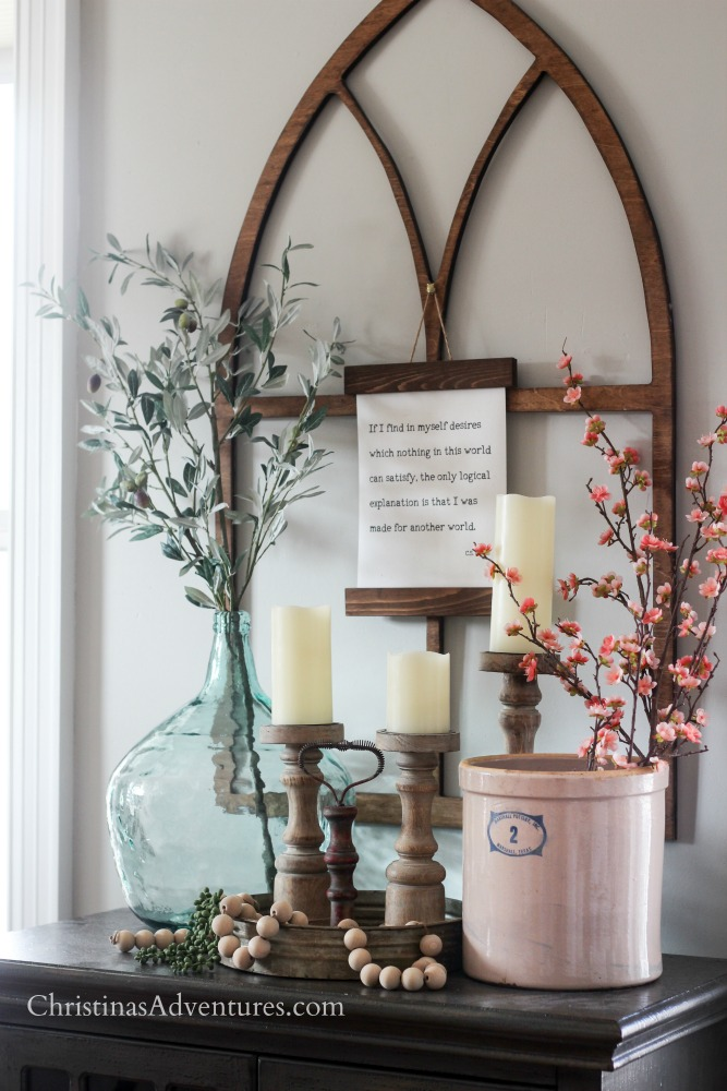 Arched window frame olive branches and weathered wood candlesticks