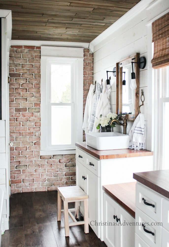 Brick wall in farmhouse bathroom and wood ceiling