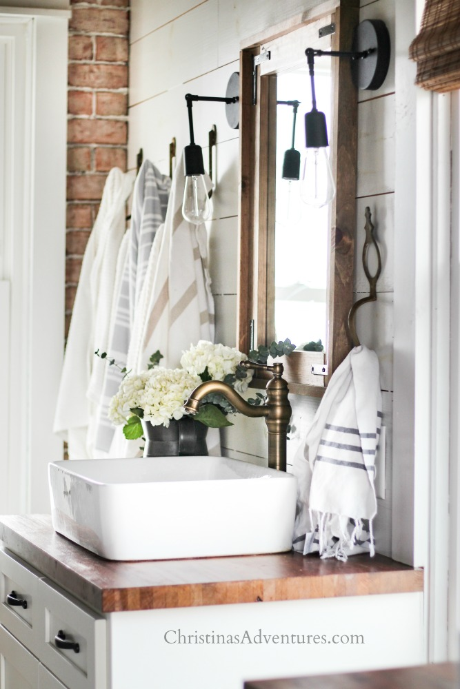 farmhouse bathroom with brick wall vessel sink and aged brass faucet