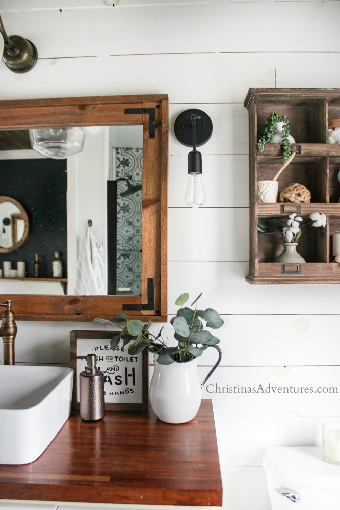 wood cubby over the toilet in a farmhouse bathroom with patterned tile shower