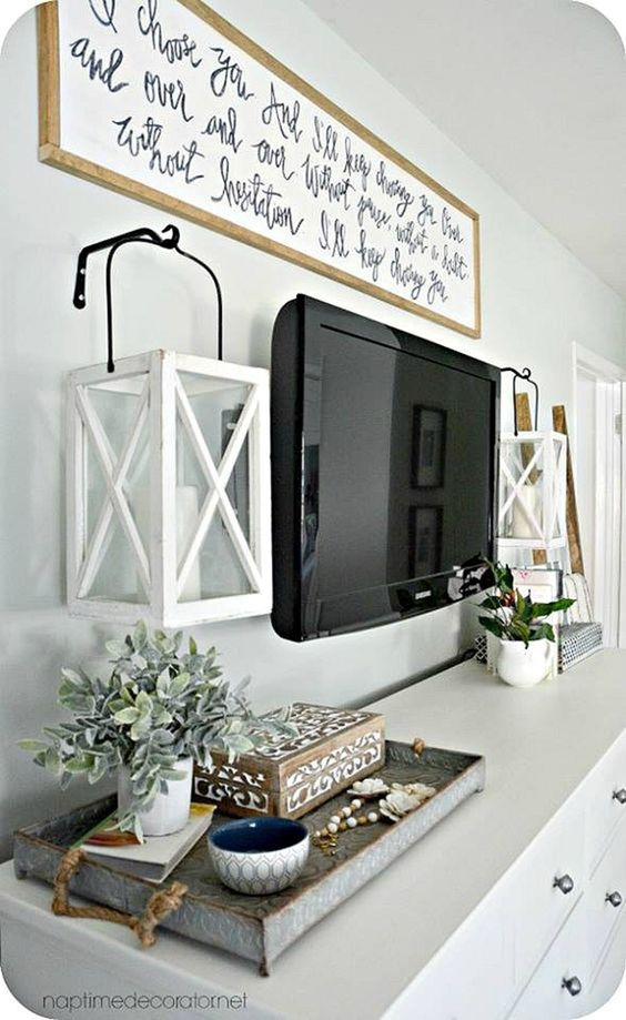 Use lanterns on the sides of the TV and a large sign above it for a unique decorating idea around a TV