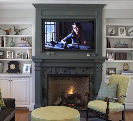 TV camouflaged with a dark gray fireplace mantel with built in bookshelves on either side