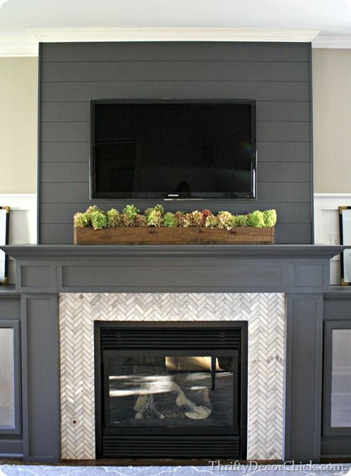 Use a dark gray shiplap wall to camouflage a TV on a wall