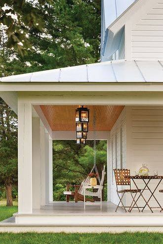 wide farmhouse front porch with a wood ceiling, lanterns, and white columns