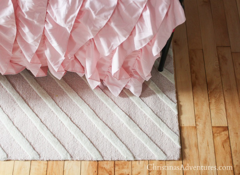 pink ruffle bed with pink and white chevron rug