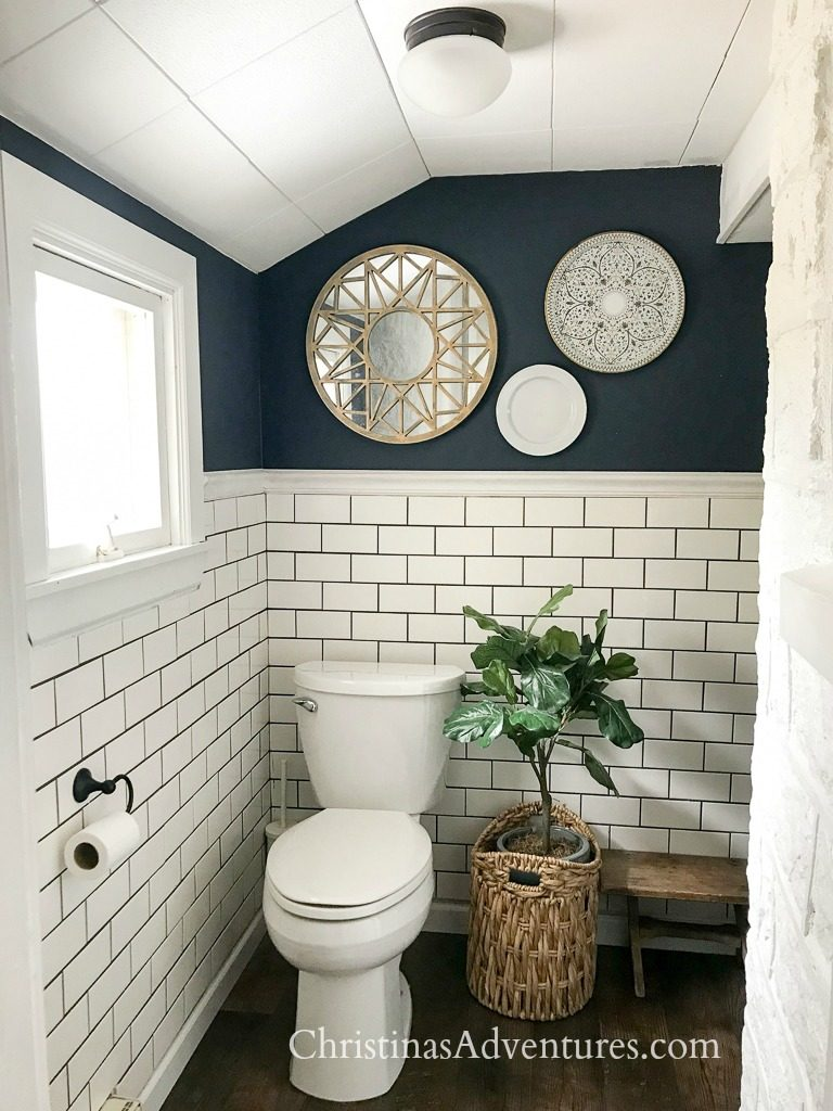 hale navy benjamin moore dark paint in small bathroom with white subway tile