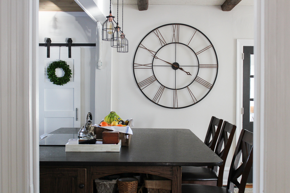 sliding barn door in a farmhouse kitchen with an oversized wall clock